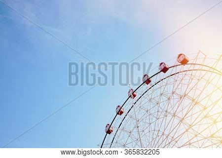 Ferris Wheel With Bright Red Booths On Background Of Serene Clear Blue Sky With Sunflare As Symbol O