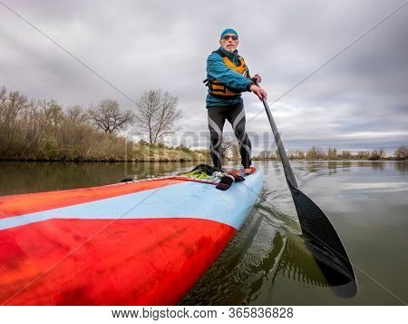 solo senior male paddler with his stand up paddleboard on a shore of calm lake, solo paddling as fitness and training with social distancing, POV from action camera