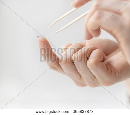 A Hand With Tweezers Reaches For The Contact Lens On The Index Finger Of The Other Hand. Using Conta