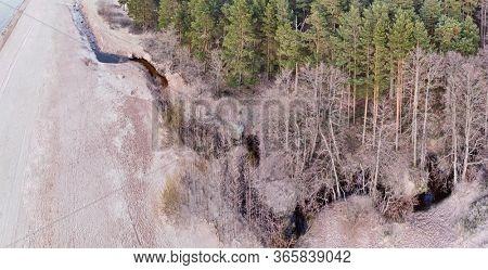 aerial view of brook between winter trees