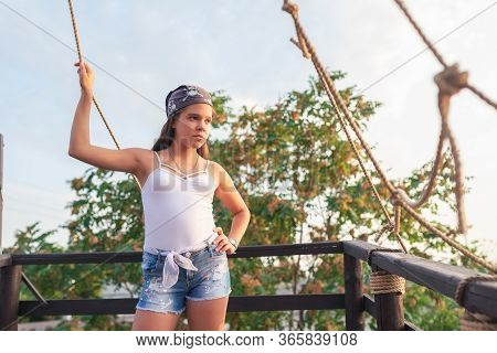 Ute Teenager Girl In Shorts And A Hat Stands On The Open Balcony Stylized As A Pirate Ship L Warm Su