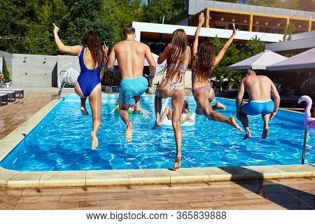 Happy Friends Jumping And Splashing In Swimming Pool With Inflatable Floats In Luxury Resort. Young