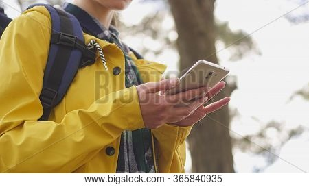 Close Up Of Young Woman Hiker Using Her Smart Phone While Enjoying Her Weekend In Forest
