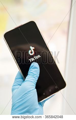 Tver, Russia-may 7, 2020, The Tik Tok Logo On The Smartphone Screen In Hands. Hands In Medical Glove