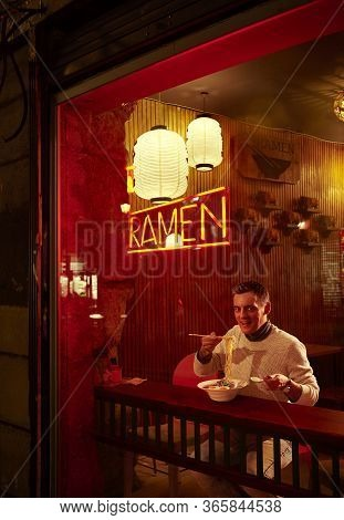 A European Man Eating Ramen In Front Of The Storefront Of A Japanese Restaurant At Night.