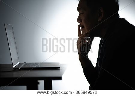 Silhouette Asian Man Working On Laptop. Beared Man Works From Home On Notebook. Freelancer Man Blogg