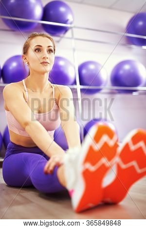 Beautiful athletic girl is doing stretching exercises in a fitness center. Sports and healthy lifestyle. Aerobics and fitness. Fitness trainer portrait.