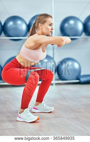 Beautiful athletic girl is doing exercises using fitness gum in a gym center. Sports and healthy lifestyle. Aerobics and fitness. Fitness trainer portrait.