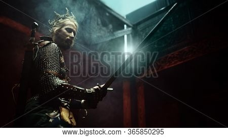 Fantasy medieval knight in armor and crown is fighting with a sword in his hands. The Witcher man.