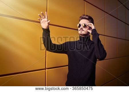 Urban style. Portrait of a stylish young man in black pullover and round mirror sunglasses raised his hand to touch something standing on a street by the yellow industrial wall. Male fashion.