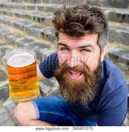 Friday Relax Concept. Man With Beard And Mustache Holds Glass With Beer While Sits On Stone Stairs.