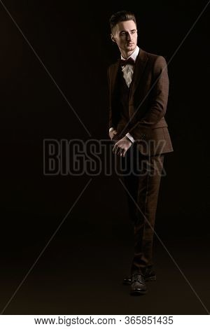Full length portrait of a handsome man in elegant classic suit and bow tie on a black background. Business style. Men's fashion.