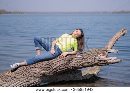Ygirl On A Warm Spring Day.oung Attractive Girl With Brown Long Hair, Sitting On A Log Above The Riv