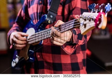 Male Hands Holds Bass Guitar, Play Music In Club Atmosphere Background. Musician, Artist Play Electr