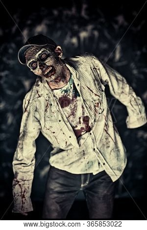 Scary bloodthirsty zombie man in a ruined building. Horror. Halloween.