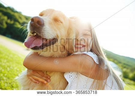 A Child With A Dog In Nature. Girl Playing With A Dog On Green Grass At Sunset Time.