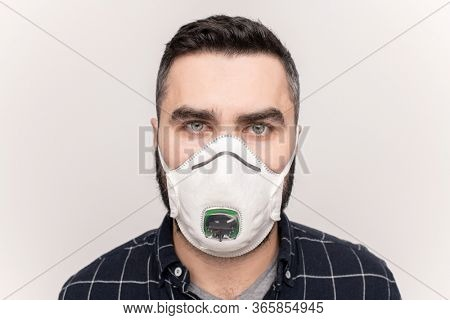 Young man in respirator and casual checkered shirt looking at you while standing in front of camera over wite background