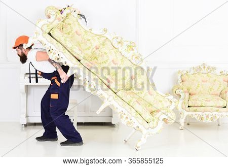Strong Bearded Guy Carrying Antique Furniture With Flowery Print. Side View Mover Lifting Long Vinta