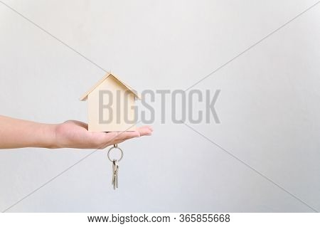 Hand Holding Wooden House And Home Keychain. Property Investment And House Mortgage Financial Real E