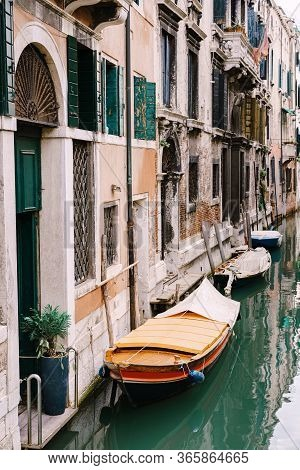 Moored Boats At The Walls Of Houses In The Water In Venice. Narrow Deserted Canal Between Houses, Az