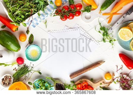 Fresh food ingredient for cooking healthy meals at home and lists paper with pen. Food frame with copy space, top view.