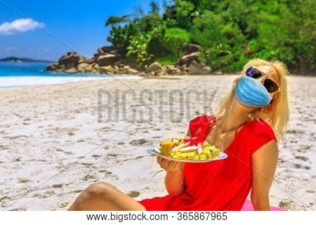 Girl Holding Fresh Fruit Dish At Seychelles With A Surgical Mask During Covid-19. Happy Lifestyle At