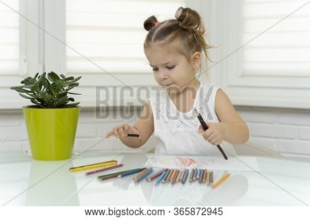A Little Girl Aged 3-4 Years Draws At The Window At The Table With Pencils.selects The Color Of The
