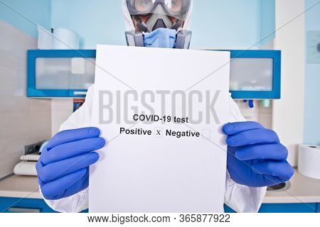 Doctor In Protective Suit Uniform And Mask Holds Coronovirus Test Results. Coronavirus Outbreak. Cov