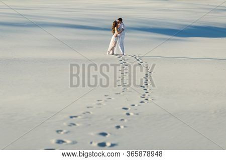 Newlyweds Walk Barefoot On The Sand In The White Desert. Love In The Desert Newlyweds.