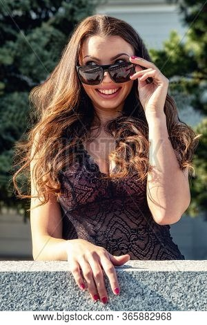 Pretty Young Woman With Big Breast And Smiling Face Looking Through Sunglasses.