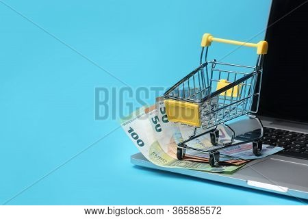 Shopping Cart With Euro Banknotes On Laptop On Blue Background, Shopping Online Concept.