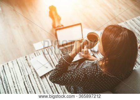 Businesswoman Dressed In Pajamas Enjoying Morning Coffee On The Floor Office With Laptop, Papers Top