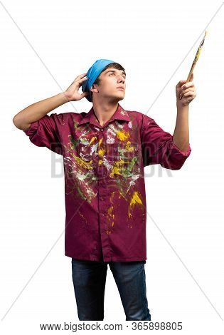 Young Male Painter Artist Holding Paintbrush. Portrait Of Painter In Dirty Shirt And Bandana Standin