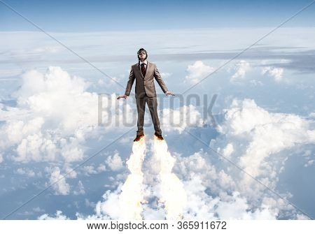 Businessman In Suit And Aviator Hat Flying In Blue Sky As Superhero. Corporate Manager As Superhero