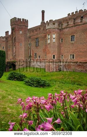Purple Flowers And Herstmonceux, East Sussex, England. Brick Herstmonceux Castle In England (east Su