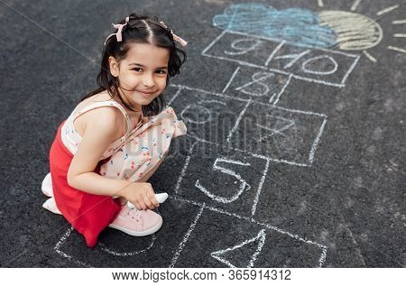 Smiling Little Girl Drawing With Chalk Hopscotch On Playground. Child Playing The Game Outside. Kid