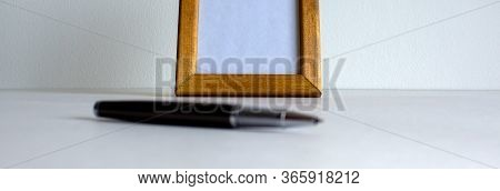 Pen On Beautiful White Fon. Wooden Picture Frame And Cap In The Background.