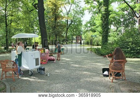 Lodz / Poland. 18 June 2019: Girl Sells Ice Cream In Park And Other Plays The Violin. People Have A