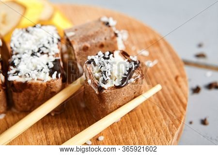 Chocolate pancake with kiwi, coconut flakes on wooden board top view. Spring roll with mascarpone cheese, cream cheese, chocolate topping and condensed milk closeup. Sweet meal with banana decoration