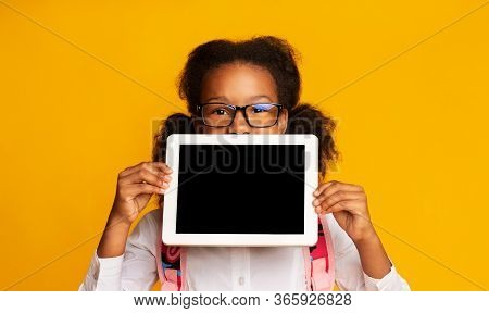 Online School And E-learning. Schoolgirl Holding Digital Tablet With Blank Screen Recomending Web Cl