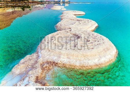 Early morning at the resorts of the Dead Sea. Picturesque white paths from evaporated salt. Azure sea water is full of healing salts. Israel. Concept of ecological, medical and photo tourism