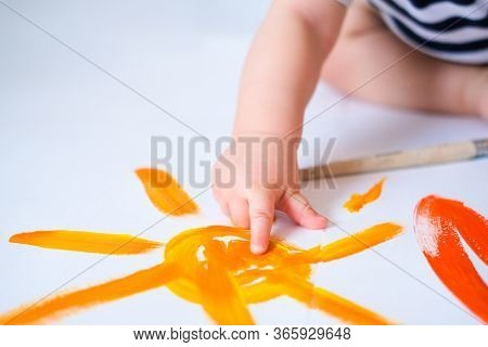 Cropped Baby Crawls On The Floor Playing With Paint, Showing Finger Yellow Painted Sun Close Up. Hap