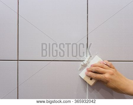 Grouting Between Tiles In The Bathroom. Female Hand Holds A Spatula. Repairs