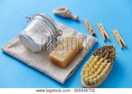 cleaning stuff, sustainability and eco living concept - natural brush, washing soda in glass jar and laundry soap on canvas with wooden scoop and clothespins on blue background