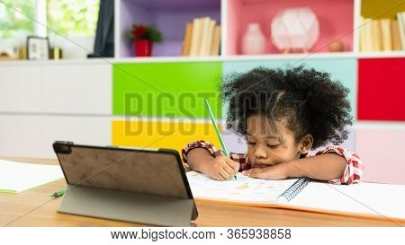 Young African American Kid Girl Studying Using Digital Tablet, Preschool Child Study At Home School.