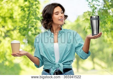 sustainability, eco and green living concept - portrait of happy smiling young woman in turquoise shirt comparing thermo cup or tumbler with disposable paper coffee cup over natural background