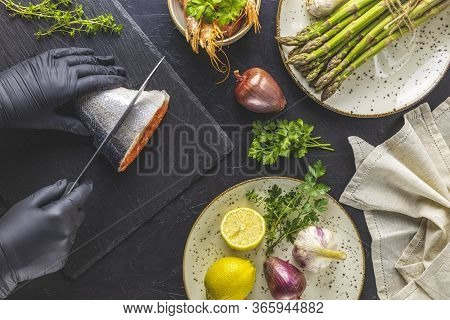 Hands In Black Gloves Cut Trout Fish On Black Stone Cutting Board Surrounded Herbs, Onion, Garlic, A