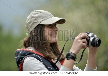 Portrait of young woman photographying nature