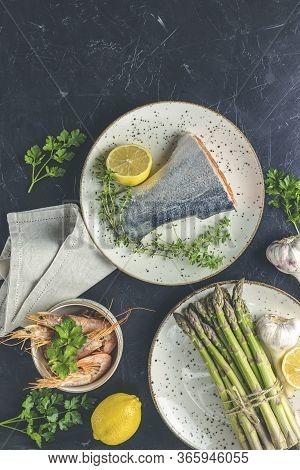 Trout Fish  Surrounded Parsley, Lemon, Shrimp, Prawn, Asparagus In Ceramic Plates. Black Concrete Ta