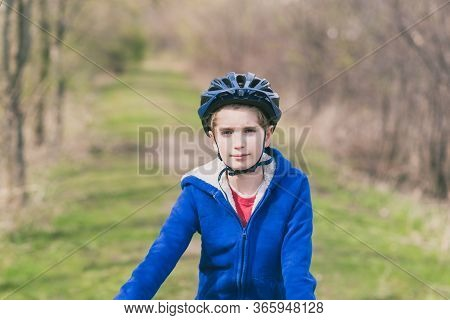 Portrait Of A Young Boy Wearing A Bicycle Helmet And A Blue Sweatshirt On A Sunny Day In The Park